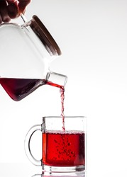 Red tea is poured into a beautiful transparent mug from a glass teapot on a white background, close-up, vertical orientation