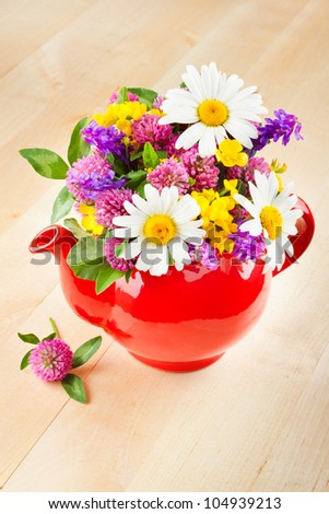 red teapot with bouquet of healing herbs and flowers, herbal medicine