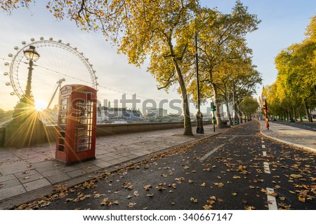 Red Telephone booth and autumn leaves at sunrise. Fall in London, England