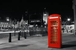 Red Telephone Booth at night, Victoria Tower in the distance. Red phone booth is one of the most famous London icons.
