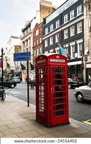 Red telephone box on busy London street in England