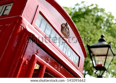 red telephone box with old fashioned london street light in soft focus