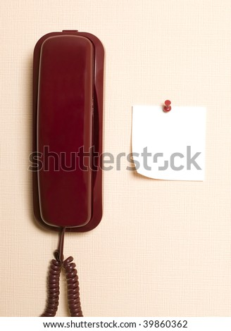 Red telephone is hanging on light brown wall