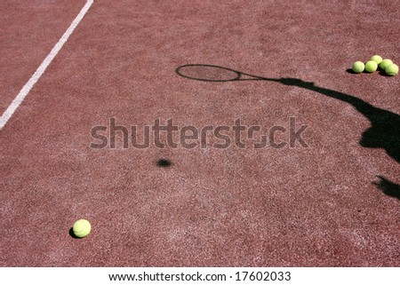 Red tennis court with yellow tennis balls and the shadow of a player