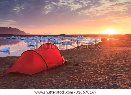 Red tent during a beautiful sunrise at the Jokulsarlon lagoon on Iceland. #318670169