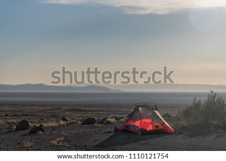 Red tent in the middle of the Atacama Desert during Sunset with endless salt plain and hazy mountains in the distance