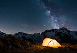 Red tent in the mountains under the night sky and the milky way.