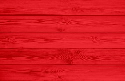 Red texture of pine wood grain with knots. Vintage red abstract background with wood pattern.