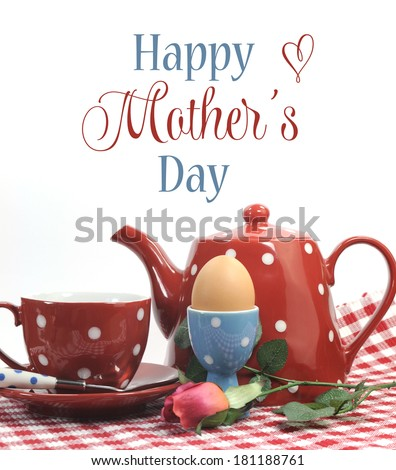 Red theme Happy Mothers Day breakfast in bed with tea cup, tea pot and egg in red and blue polka dot china with sample text or copy space.