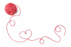 Red thread, heart and tangle on light wooden background