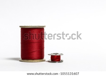Red thread on a spool with corresponding bobbin - Shutterstock ID 1055131607
