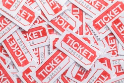 Red Tickets Laying in Large Pile Background.
