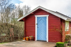 Red tiny house or shed at a plot of an allotment. Early spring time. Small red shack with the blue door, white frames, flat wooden terrace and flowers. Hut painted in traditional Swedish red color.