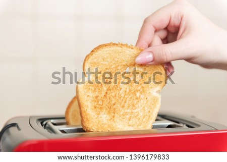 Red toaster with toasted bread for breakfast inside. Hands Girl pulls out ready toasts.  #1396179833