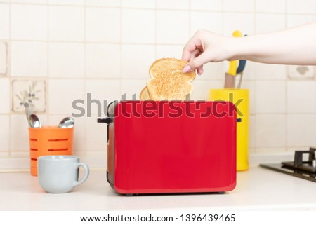 Red toaster with toasted bread for breakfast inside. Hands Girl pulls out ready toasts.  #1396439465