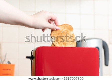 Red toaster with toasted bread for breakfast inside. Hands Girl pulls out ready toasts.  #1397007800