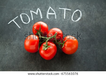 Red tomaRed tomatoes on green branch for cooking laying on blackboard with letters written by chalk.toes on green branch for cooking laying on blackboard with letters written by chalk. #675561076