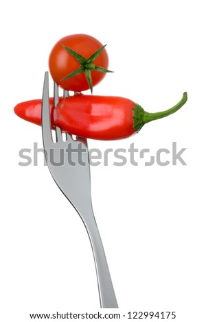 red tomato and chili pepper on a fork against white background