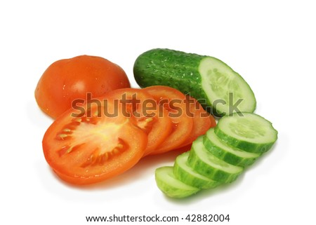 red tomato and  green cucumber chopped circles lying on a white plate