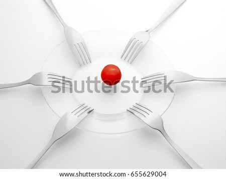 Red tomato and six black and white forks. Sharing, competition, shortage and contention concept. On white background Stock photo ©