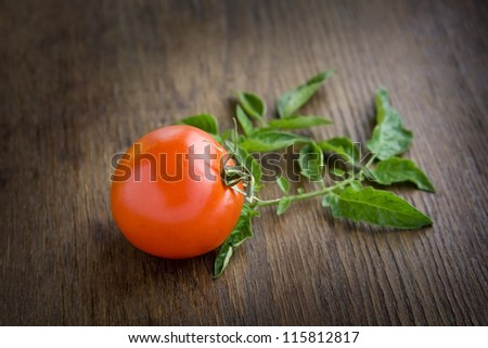 Red tomato lying on a dark brown table.