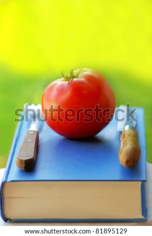 Red tomato on a book, knife and fork