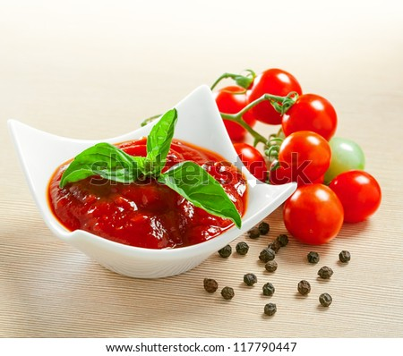 Red tomato sauce in a pan and ingredients