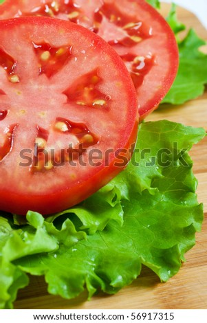 Red tomato slices and salad leaves on chopping board