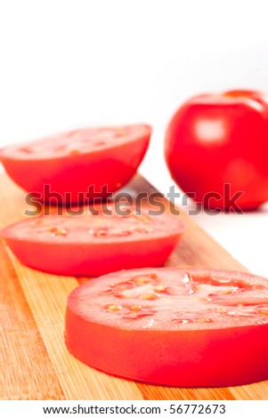 Red tomato slices on chopping board - stock photo