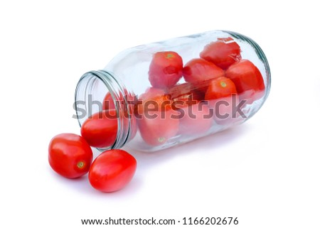 Red tomatoes in a glass jar for preservation isolated on white background