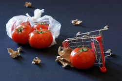 Red tomatoes, overturned supermarket carts and torn pieces of paper are scattered against a dark background. Concept of trade problems, farm strikes and anti-globalization. Close-up
