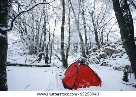 Red tourist tent in winter forest