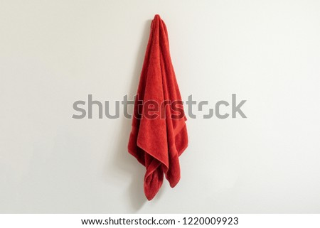 Red towel on a towel hook against a white wall