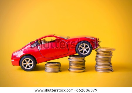 Red toy car rides up a pile of coins #662886379