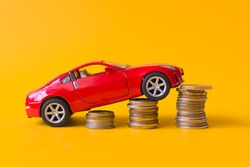 Red toy car rides up a stack of coins