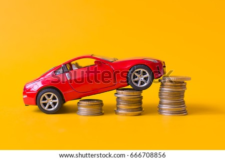 Red toy car rides up a stack of coins #666708856