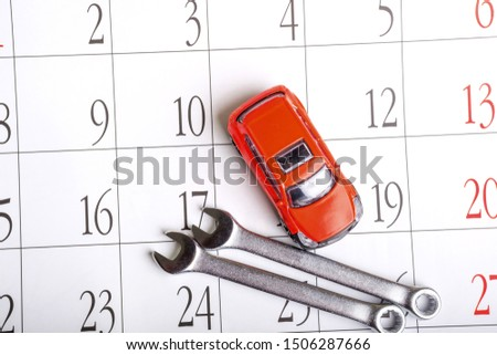 red toy car top view and wrenches on the calendar sheet. routine maintenance and inspection of vehicles on schedule