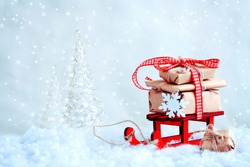 red toy sled with a pile of gifts, christmas tree, snow, retro style background