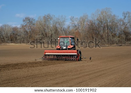 red tractor and seeding attachment on the field