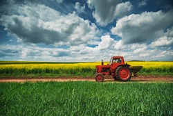 Red tractor in a field and dramatic clouds