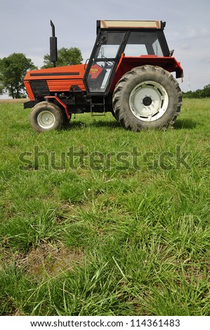 Red tractor on the meadow