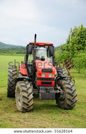 Red tractor parked on a grass field (front) - stock photo