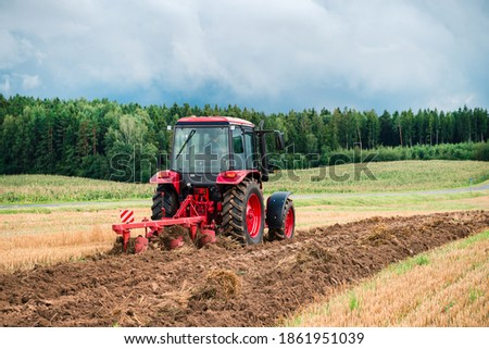 Red Tractor Plowing in Autumn, Farmer plowing stubble field in tractor preparing plows the land, agricultural works at farmlands, agriculture tractor-landscape Foto stock ©