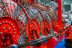 Red tractor rotary wheel hay and tedding rakes at farming exhibition, trade show. Agriculture machinery equipment concept