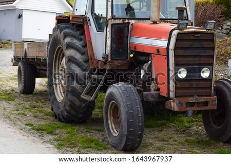 Red tractor with a trailer. Agricultural machinery.