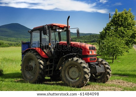 Red tractor with blue trailer on a grass field
