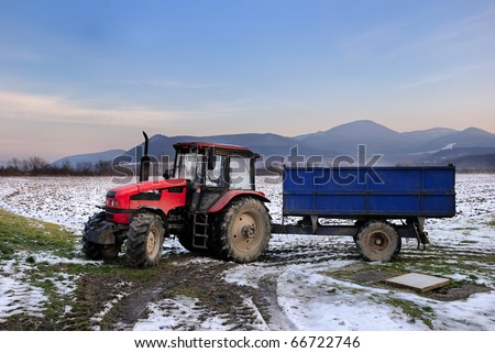 Red tractor with blue trailer on a snowy field