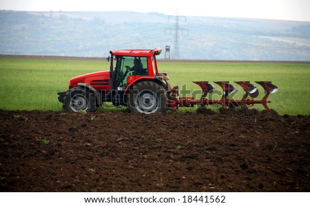 Red tractor working at field