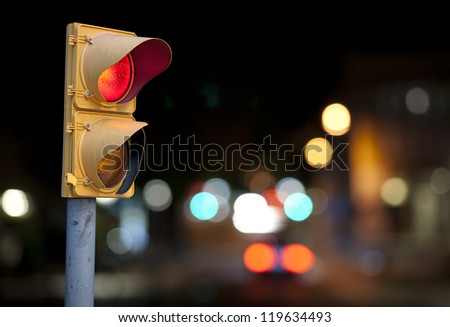 Red traffic light at night with city lights in background
