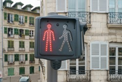 Red traffic light. Image of the red colored figurine of a man. Stop sign for pedestrians. Architecture of ancient city as background.